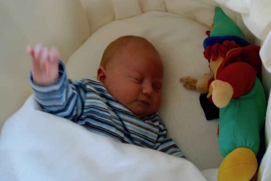 Baby liegt im Bett mit Kuscheltier