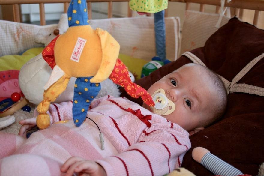 Baby mit Spielzeug im Babybett