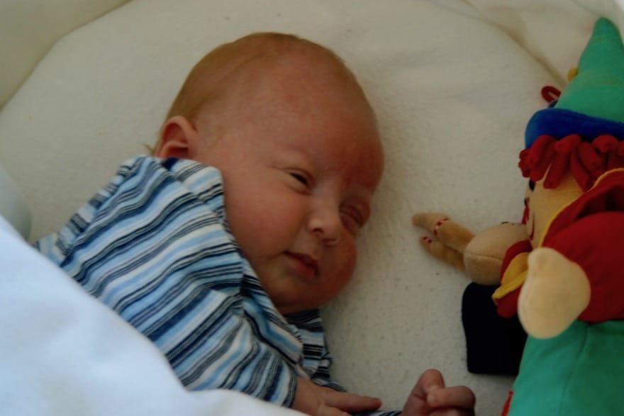 Baby liegt im Kinderbett