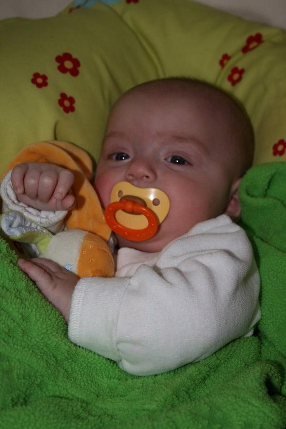 Baby mit Schnuller im Bett